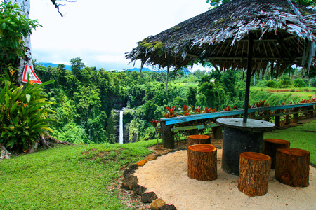 Colourful tropical paradise garden in Oceania, wooden shelter with palm thatch roof, jungle forest lookout, Sopoaga Falls resort in Samoa, Upolu Island