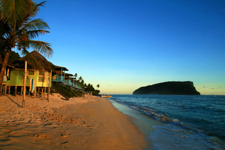 Pacific Island tropical sandy beach with traditional beach fales resort accommodation during beautiful colourful sunset sky twilight, Samoan Islands