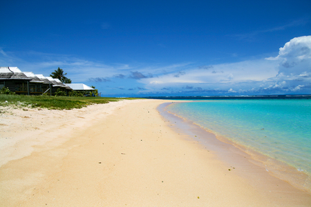 Beachfront fale cottages on tropical white sand beach and shallow water of blue ocean lagoon, Savai'i island South Pacific