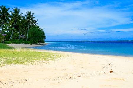 Exotic sandy beach view during sunny hot day in Polynesia, warm blue waters of Pacific ocean, Manase Beach fales