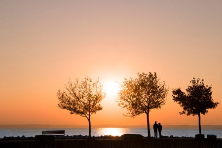 Awesome natural sunset over the sea with water reflection of golden sun above the skyline, silhouettes of autumn trees and romantic couple of people watch colourful sky scenic background from the pier Stock Photo