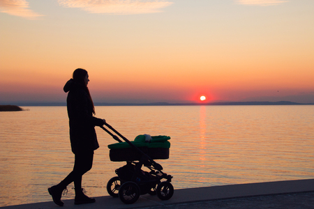 Silhouette of woman pram walking, mother is pushing the stroller on walkway while admiring colourful sunset sky and setting sun over the sea water landscape on background Stock Photo
