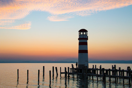 Low horizon romantic sunset sky over the lake landscape with red white lighthouse architecture and dock pillars in the water, beautiful warm colours of the largest lake in Central Europe, Neusiedl See Stock Photo