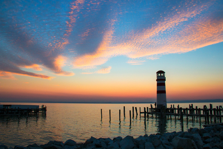 Sunset sky over the sea horizon landscape with lighthouse landmark with wooden dock pillars standing in the water, twilight scenic view from pier of Podersdorf am See, Neusiedl lake in Austria Stock Photo