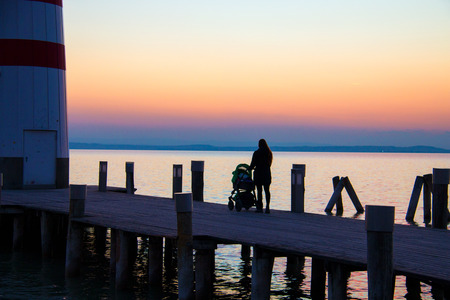 Sunset lake pier with dock pillars and stroller walking woman silhouette in front of twilight sky seascape