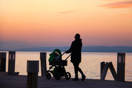 Woman walks with pram silhouette, mom standing on pier walkway, holding a stroller with baby and watching colourful yellow orange sky sunset above sea horizon