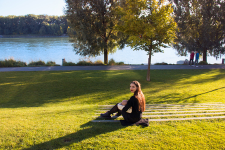 Young happy mother, white female in black breastfeeding and caring little baby sitting outside in the middle of green lawn at Danube river public promenade during wonderful autumn day Stockfoto