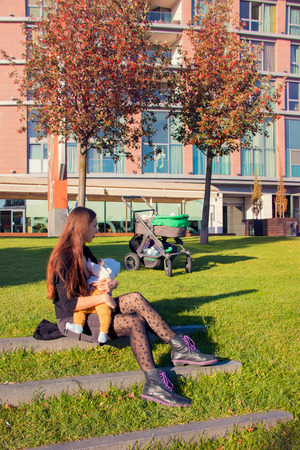 Young mother in black stickings and boots sitting on lawn outside next the stroller and breastfeeding her baby on public, autumn trees with red leaves and city building behind