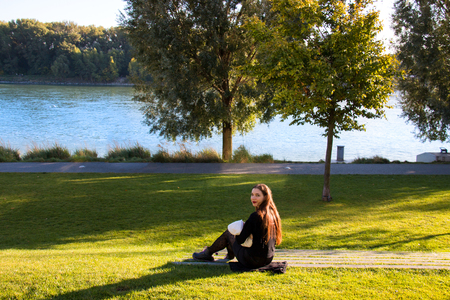 Beautiful happy mother holding and breastfeeding baby in natural park promenade on shore of the river Danube, sitting outdoor at green lawn on sunny autumn day Stock Photo