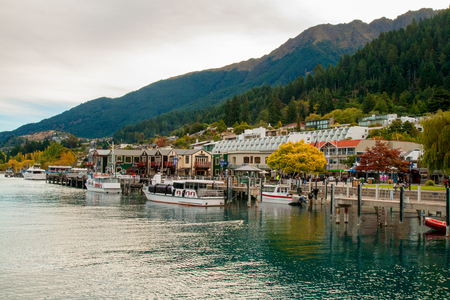 Central part of Queenstown resort town on lake Wakatipu in Southern Alps, docked boats and lakeside city park, alpine architecture, colourful autumn in mountains, New Zealand Stock Photo