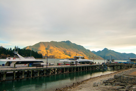 Beautiful golden sunset lights on mountains, luxury boats docking on lake Wakatipu, Town of Queenstown Wharf, pier in city centre, dock for boaters, South Island of New Zealand tourist destination Stock Photo