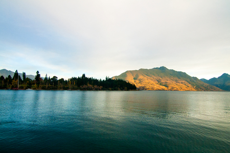 Awesome nature scenery of mountain lake Wakatipu, autumn forest and Cecil Peak on the background, Evening sunset hours in Queenstown New Zealand Central Otago