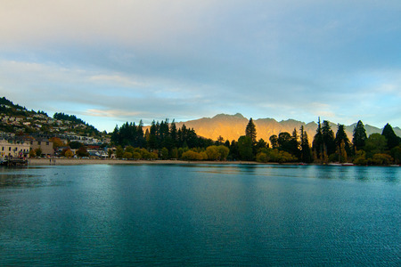 Queenstown New Zealand famous resort town in Otago and iconic mountain range the Remarkables above blue Lake Wakatipu, romantic sunset autumn scenery with golden sun light