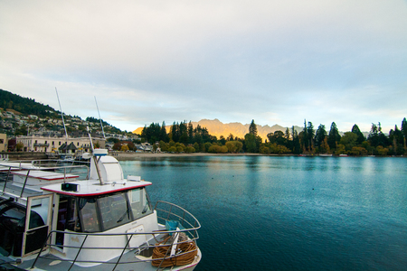 Queenstown New Zealand tourist destination city, evening view with golden sun reflection on the Remarkables mountains range, luxury boat dock in front on the lake Wakatipu