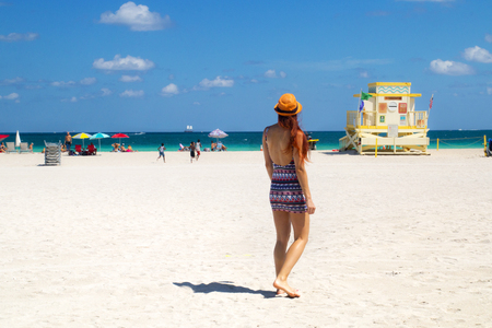 Holiday at Miami Beach Florida. Back view of red hair woman in fashionable style summer outfit, lifeguard tower, children and sunbathing people, Atlantic ocean coast on sunny weather day