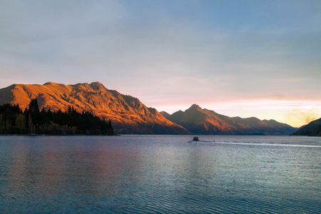 Setting sun in mountains of Southern Alps, romantic sunset at Lake Wakatipu golden rays reflection on Cecil Peak and Walter Peak, Queenstown New Zealand Stock Photo - 111393868