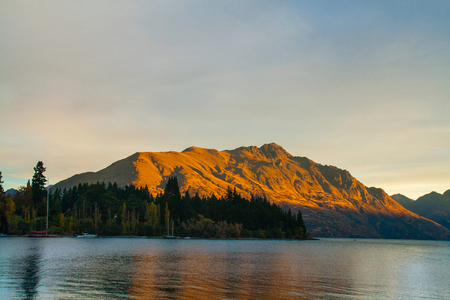 Mountain coloured by golden sun, autumn trees above the lake Wakatipu with beautiful reflection on water, Cecil Peak famous Queenstown city landmark, Otago, South Island of New Zealand