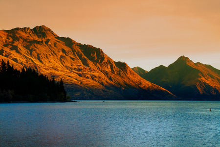 Cecil Peak, Walter Peak and Lake Wakatipu on sunset light in Queenstown tourist adventure and holiday destination in New Zealand, awesome nature background of beautifully coloured by golden sunlight