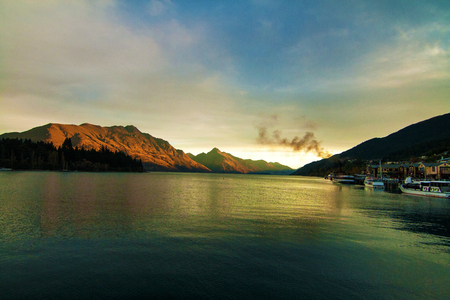 Awesome sunset view of southern Alps landscape with Lake Wakatipu, mountains of Cecil and Walter Peak with famous Queenstown steamship, New Zealand South Island, holiday resort city of Queenstown