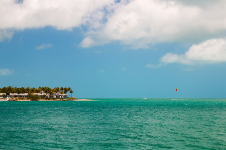 Turquoise blue sea horizon and island with sandy beach, palm trees and beachfront house cottages, Sunset Key in the Key West, Florida USA