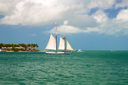 Sailboat with big white sails sailing on clear blue water of tropical paradise, holiday island sandy coast of Sunset Key resort island, Florida Key West, Mexican Gulf