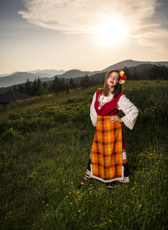 Beautiful young girl dressed in a traditional Bulgarian folklore costume in the mountain on summer sunset
