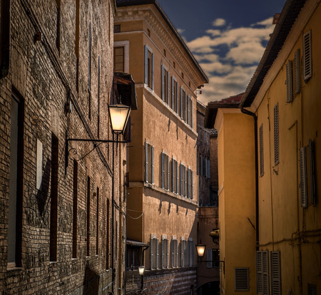 lighted up Street lights in Siena, Italy on dusk Stock Photo