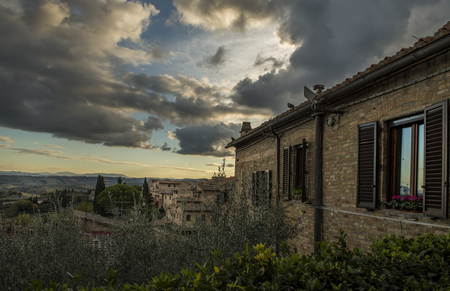Architecture of San Gimignano, Italy on sunset with dramatic clowdy sky