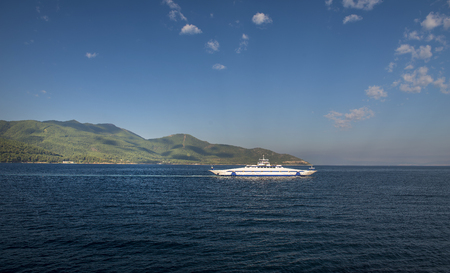 Ferry boat transporting people to Tasos island, sumer time, clear blue sky