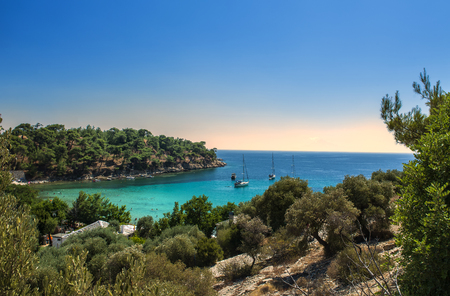 yachts in the seashore island with people swiming in turqoase water, panoramick view