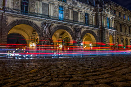 Cars light traces at night in front of the Louvre, Paris, France
