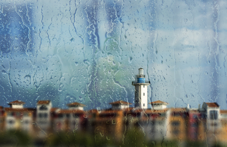 Raindrops on window, light tower background on focus
