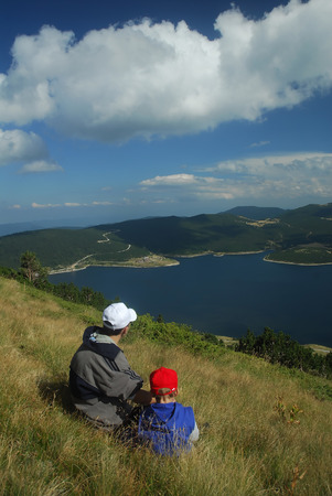 Father and son looking the lake