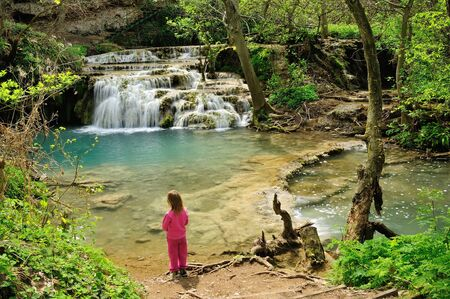 The boy looking the beautiful river and waterfall in the forest Stock Photo
