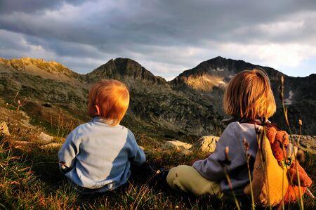 Reaching the top, two children watching the mountain peak