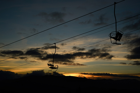 empty ski lift  chairlift silhouette on high mountain over the clouds at sunset