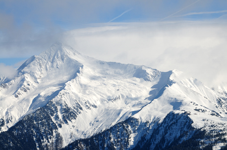 bivouac: Mountain piek with clouds and snow Stock Photo