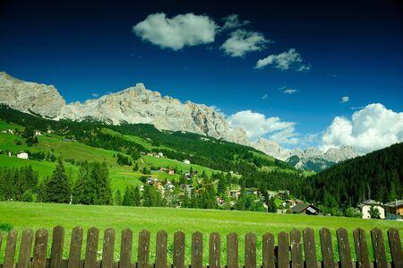 Green meadow in alpine village, Dolomites Stock Photo