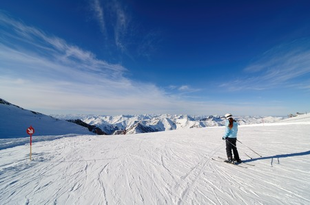 Skier on piste in Hintertux Zillertal, Austria with clouds and blue sky