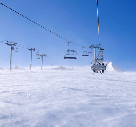 Skiers on a ski-lift in Pirin national park, Bansko, Bulgaria Stock Photo