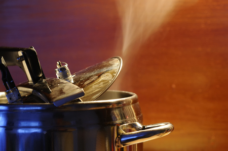 Steam escaping from lid of pressure cooker with reflection of modern kitchen. Indian style cooking rice or dhal 스톡 콘텐츠