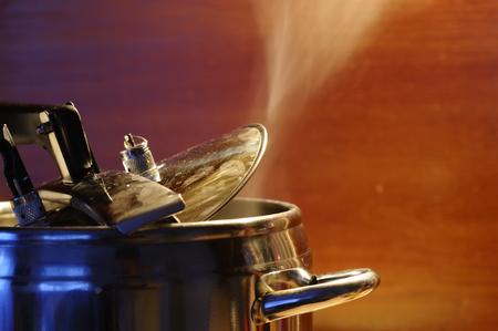Stoom die uit deksel van snelkookpan met weerspiegeling van moderne keuken ontsnapt. Rijst met rijst in Indiase stijl of dhal Stockfoto
