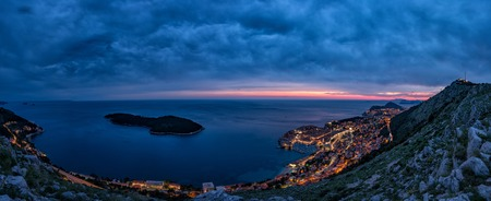 Lovely panoramic view of the old walled city of Dubrovnik with birds eye view at night. City backlit. Croatia