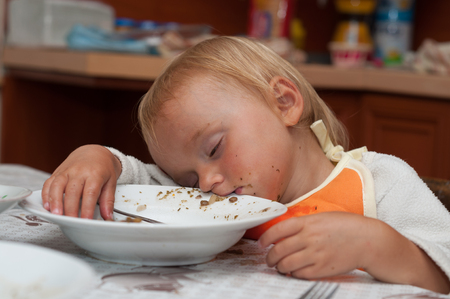 Tired young girl sleeping after lunch in the kitchen Stock Photo
