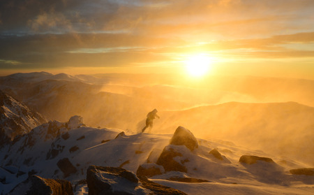 A man fights with bad weather in the winter mountains Stock Photo
