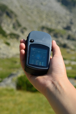 Man holding a GPS receiver in his hand. Handheld GPS devices are used predominantly in the outdoor leisure industry for walking and hiking.
