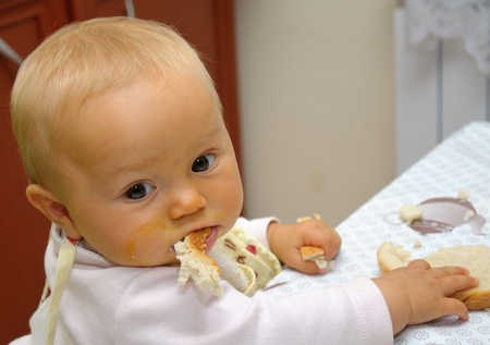 smiling baby eating food alone on kitchen Stock Photo