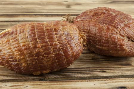 Smoked boneless pork ham hock wrapped in netting on a wooden background