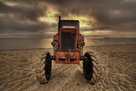 the arable land: old tractor on beach. Stock Photo