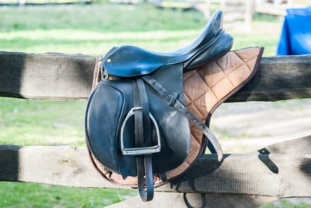 Horse saddle hanging on a wooden fence Stock Photo
